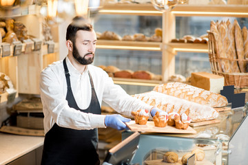 Bread seller putting maffins on the showcase standing in the beautiful store with bakery products