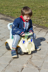 A boy drives a children's car in the park