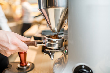 Grinding a coffee into the handle of the professional coffee machine