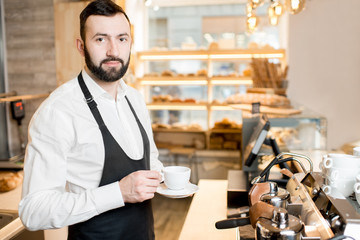 Portrait of a handsome barista standing with coffee cup in the cafe