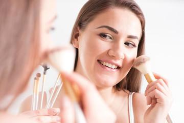 Frau schminkt sich vor einem Spiegel