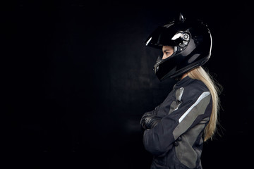 Sideways shot of attractive young blonde Caucasian female wearing styling outfit and black safety helmet crossing hands on chest, posing at blank studio wall with copy space for your advertisement