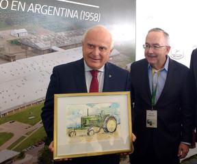 Argentina's Santa Fe province governor Lifschitz holds a picture of a John Deere tractor next to Allen, Chief Executive of U.S. tractor maker Deere & Co, during an event in Rosario