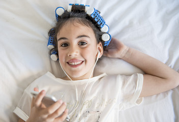 little girl posing with curlers and Smartphone
