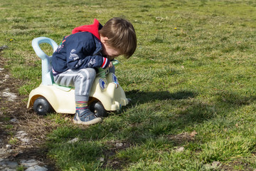 A boy drives a children's car in the park