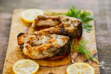 appetizing grilled fish pieces with parsley on the board