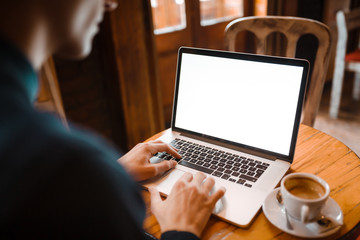 Mockup image of business man using and typing on laptop with blank white screen and coffee cup on glass table in cafe