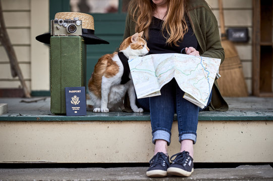 a girl looking at a map with her cat
