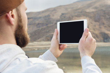 Hipster person holding in hands digital tablet with empty blank screen, man photograph on computer on background nature outdoor landscape mock up technology blur male hands tourist using gadget