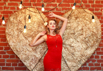 Charming woman in red dress on golden heart in studio