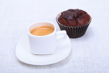 Classic espresso in white cup with chocolate muffin on white background.