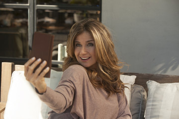 Happy adult woman taking a self portrait with mobile phone