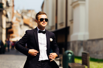 incredible groom in a black suit with a black bow tie and sunglasses against the background of the city