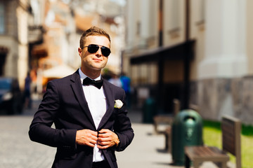 handsome groom in sunglasses unbutton the button against the background of buildings