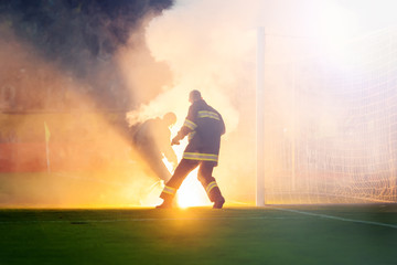 firemen extinguish fire thrown the field by fans