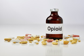 Auf einer weißen Fläche Steht eine Ampulle auf der Opioid geschrieben steht. Um die Ampulle herum liegen viele tabletten. Der hintergrund ist Weiß