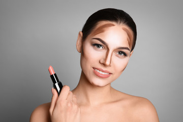 Young woman with contouring lines on her face against grey background. Professional makeup products