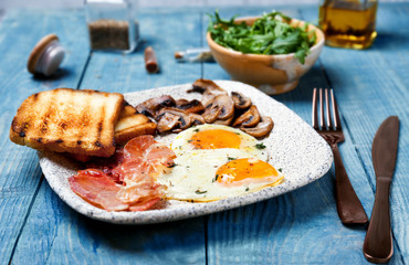 Plate with fried eggs, bacon, mushrooms and toasts on wooden background
