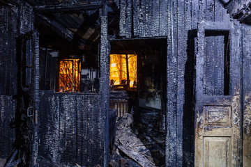 Burnt house. Burned furniture, door, charred walls and ceiling