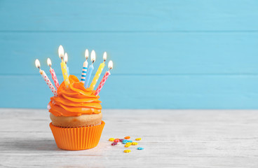 Delicious birthday cupcake with burning candles on table against color background