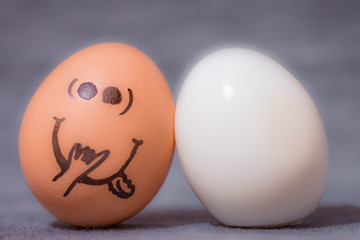 Eggs faces, drawnigs on eggs. Two eggs in love, being together, one without eggshell - nude.