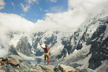 Athletic man stands at great height in front of the huge mountains and welcomes them. Victory and Freedom concept.