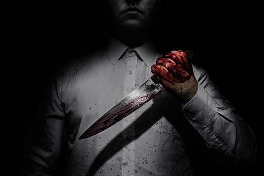 Photo of a killer in white shirt holding a bloody knife on black background with upper lighting.