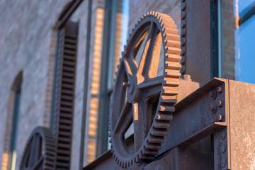 old rusty steel gears outside brick industrial warehouse