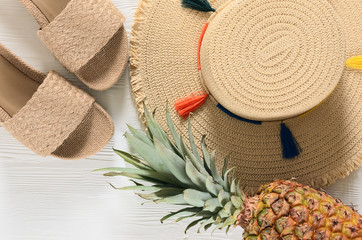 Womens summer accessories (straw hat, flip flops), pineapple on white wooden background. Fashion look, travel and summer concept. Flat lay. Natural organic stuff Wall mural