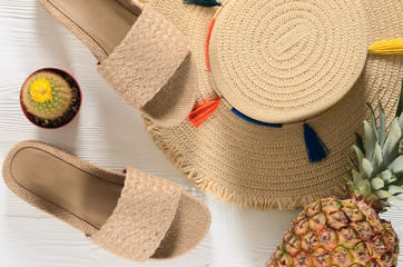 Womens summer accessories (straw hat, flip flops), pineapple, cactus on white wooden background. Fashion look, travel and summer concept. Flat lay. Natural organic stuff