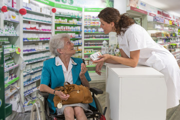 female pharmacist taking prescription from disabled woman wheelchair in a pharmafy