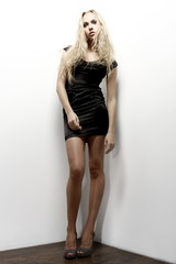 beautiful blonde woman with long legs in a little black dress on a white background, studio shot