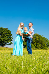 Young happy caucasian family hold baby girl, celebration fathers day outdoors. Summer, blue sky