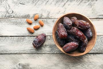 Medjool Dates and almond on wooden background. Top view. Ramadan Kareem event.