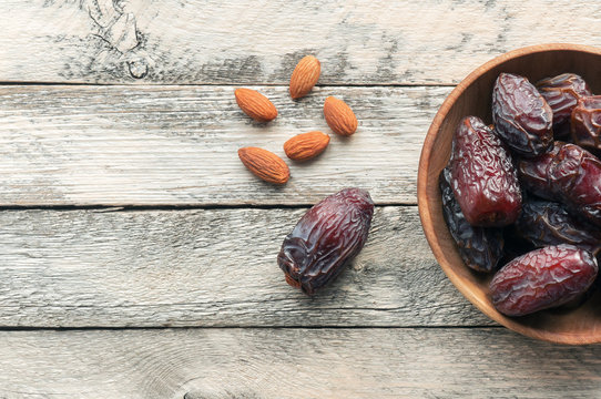 Medjool Dates and almond on wooden background with copy space. Top view.