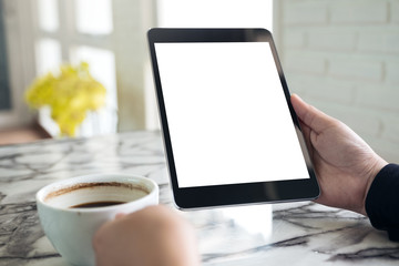 Mockup image of hands holding black tablet pc with white blank screen and coffee cup on table background