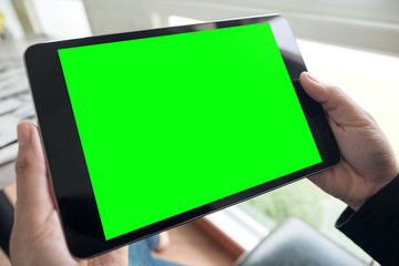 Mockup image of hands holding black tablet pc with blank green desktop screen in cafe