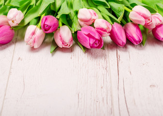 Tulips on the white wooden background
