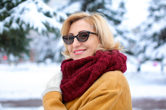 Portrait of happy mature woman in snowy park on winter vacation