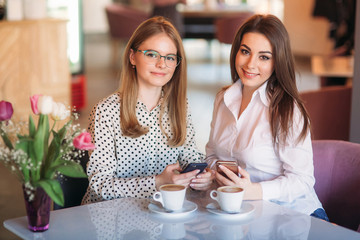 girls sitting in a cafe drinking cappuccino and using telephones