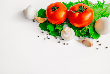 Fresh assorted vegetables tomatoes, mushrooms, garlic, lettuce leaves. Isolated on white background. Selective focus. With place for you own text message