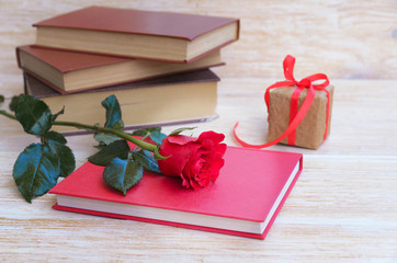 Old books and red rose, traditional gift for Sant Jordi, the Saint Georges Day. It is Catalunya's version of Valentine's day, celebrated on 23rd of April.