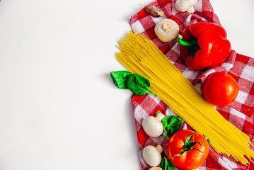 Top view of the Healthy food on the white background, healthy eating, vegetarian eating, tomato, mushrooms, bell pepper, spaghetti, garlic, basil are lie on the kitchen towel, set for cooking dinner