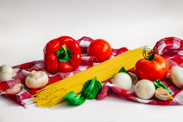 Healthy food lie on the white background, healthy eating, vegetarian eating, tomato, mushrooms, bell pepper, spaghetti, garlic, basil are lie on the kitchen towel, set for cooking dinner
