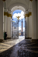 View of  Palace Square with Alexandrian column from arch of Hermitage Museum with wrought-iron gates and golden double-headed eagle, rays of sun illuminate entrance to Hermitage, St. Petersburg,Russia