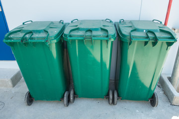 Green recycle bin or three trash bins