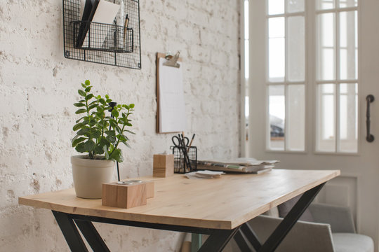 Interior of contemporary workspace with wooden table and flower and organized stationery.