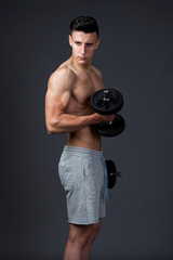 Young muscular sportsman poses in the studio shirtless in short pants