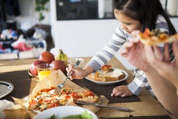 自家製のピザを食べる女の子。