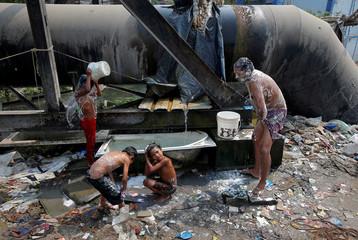 People bathe with water leaking from broken pipe valve in Kolkata